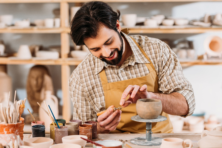 Happy potter in apron decorating ceramic bowl in workshop Stok Fotoğraf