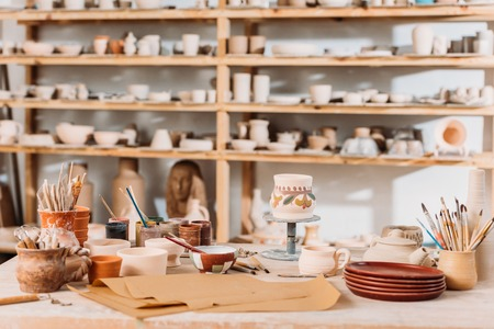 Brushes, paints and wooden shelves with ceramics in pottery workshop