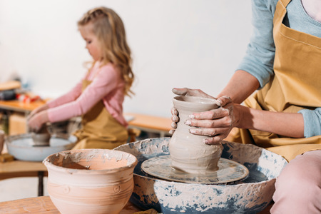 Selective focus of daughter making ceramic pot on pottery wheel with mother on foreground