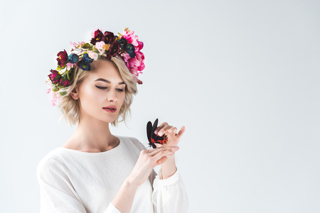 Beautiful tender young woman posing in floral wreath with butterfly on hands, isolated on grey background