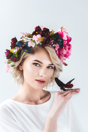 Attractive girl posing in flower wreath with beautiful butterfly on hand, isolated on grey background