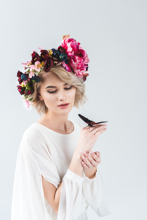 Attractive woman posing in flower wreath with butterfly on hands, isolated on grey background Reklamní fotografie