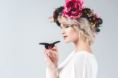 Beautiful girl posing in floral wreath with alive butterfly on hands, isolated on grey background