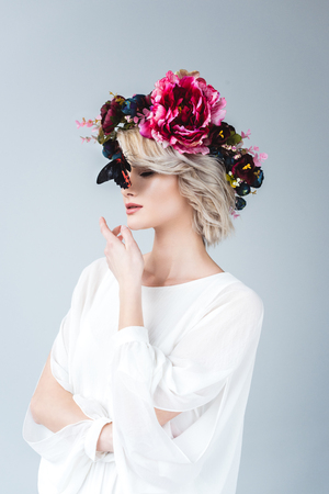 Young blonde woman posing in floral wreath with butterfly, isolated on grey background Reklamní fotografie