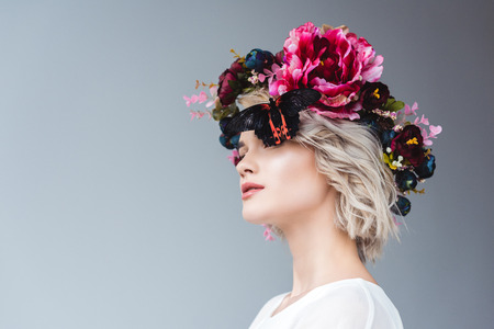Fashionable girl posing in floral wreath with butterfly, isolated on grey background Reklamní fotografie