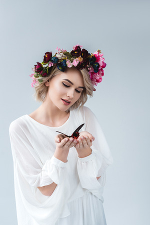 Beautiful girl posing in floral wreath with alive butterfly in hands, isolated on grey background Stock Photo