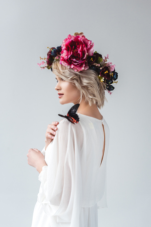 Beautiful girl posing in flower wreath with butterfly on shoulder, isolated on grey background