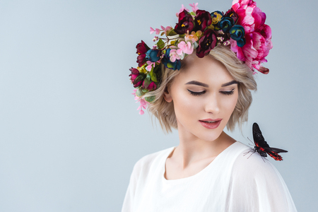 Beautiful model posing in floral wreath with butterfly on shoulder, isolated on grey background
