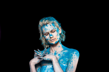 Young woman with closed eyes in blue powder, isolated on black background Stock Photo
