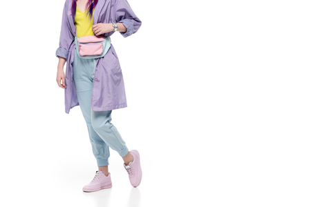 cropped shot of woman in purple trench coat with waist pack isolated on white Imagens