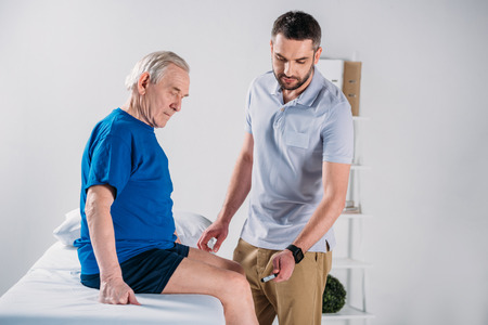rehabilitation therapist with reflex hammer checking senior mans knee on massage table Archivio Fotografico - 112249663