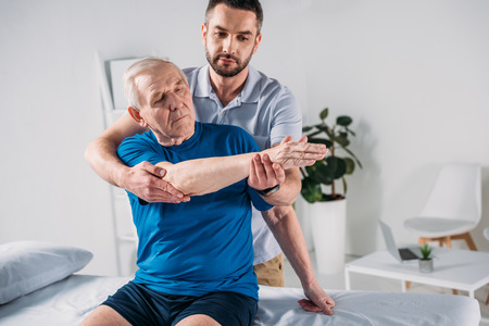 portrait of physiotherapist doing massage to senior man on massage table Stockfoto