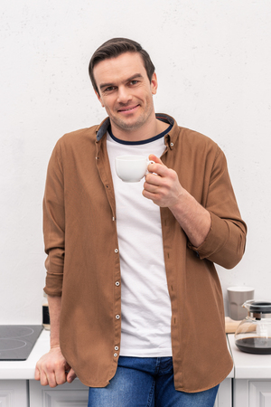 handsome adult man with cup of coffee on kitchen