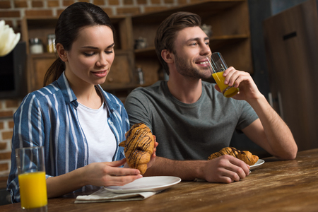 Couple drinking juice and eating croissants by kitchen table