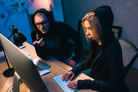 confident couple of hackers working on malware together Imagens
