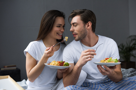 Smiling man and woman eating eggs on breakfast in bed Stock Photo