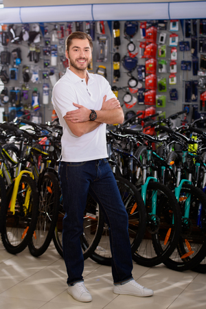 handsome young man standing with crossed arms and smiling at camera in bicycle shop