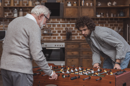 adult son and senior father playing table soccer at home 版權商用圖片