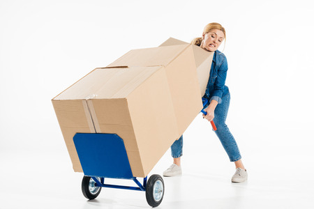 Attractive woman trying to push delivery cart with boxes isolated on white