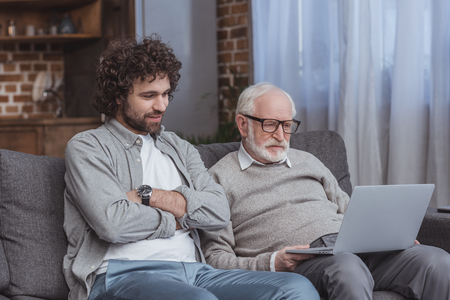 adult son and senior father using laptop on sofa at home