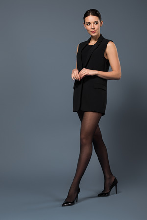 Attractive woman in black pantyhose and vest on dark background