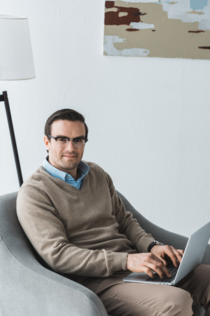 Man in glasses sitting in chair and working on laptop Stock Photo