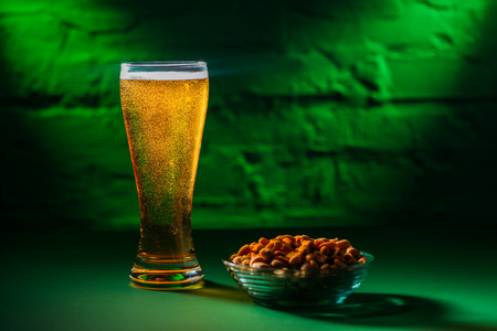 close-up view of glass with fresh cold beer and salted peanuts on plate Stock Photo