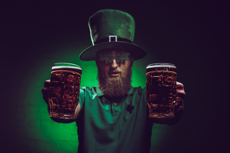 close-up view of bearded man in green irish hat holding glasses of beer