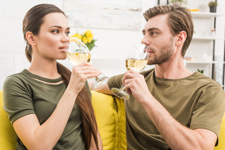 young couple drinking wine together on couch at home Фото со стока