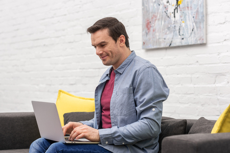happy adult man using laptop on couch at home