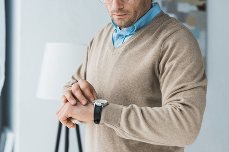 Man in glasses and casual clothes looking at his watch