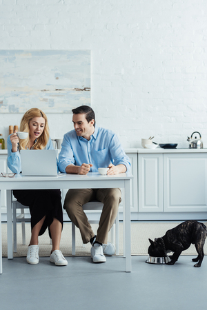 Couple drinking coffee and talking by kitchen table with laptop while their Frenchie eating Reklamní fotografie