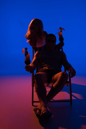 Silhouette of woman leaning on chair with man and holding cocktails on blue background in dark light