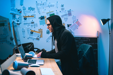 side view of hooded young hacker working with computer