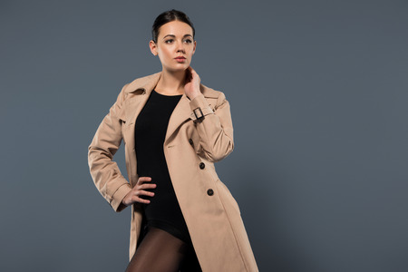 Young woman wearing beige trench posing isolated on dark background