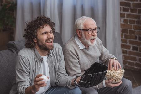 Hijo adulto y padre senior animando al equipo de béisbol y viendo el juego en casa