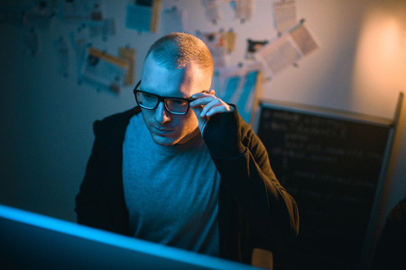 high angle view of young hacker developing malware in dark room