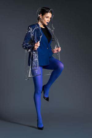 Girl wearing transparent raincoat and heel shoes on dark background