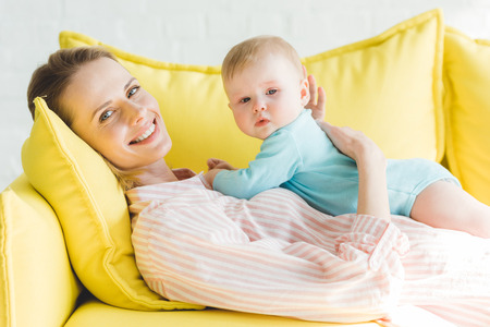 Smiling mother with infant daughter on yellow sofa