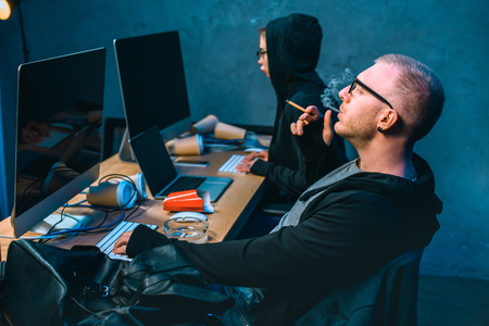 male hacker working on malware with accomplice and smoking