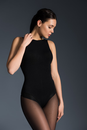 Pretty woman wearing black pantyhose and bodysuit posing isolated on dark background