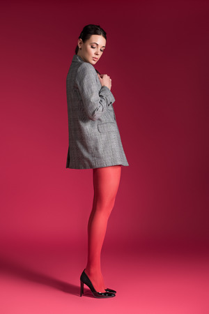 Woman with thin legs in red nylon tights on red background