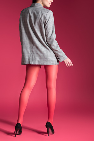 Woman posing in red pantyhose and grey jacket on red background Stock Photo