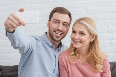 portrait of smiling mother and grown son taking selfie on smartphone t home