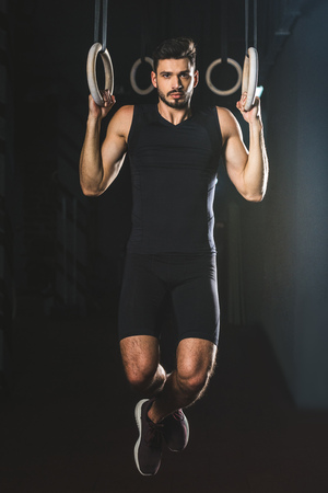 Front view of sportsman doing exercise on gymnastic rings in sports center