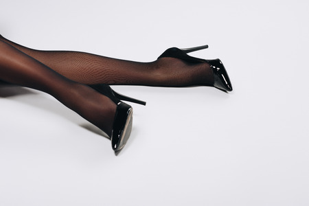 Female legs in black pantyhose and heel shoes on white background Stock Photo