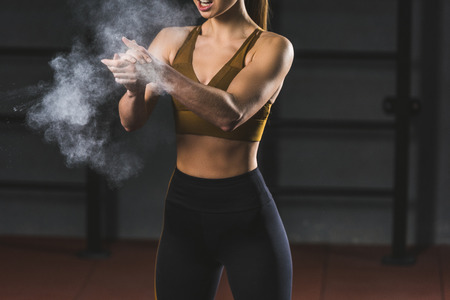 Cropped image of young sportswoman spreading chalk powder in hands for exercising in sports hall Banco de Imagens