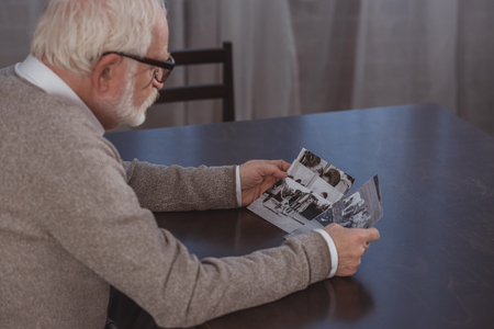 side view of grey hair man sitting at table and looking at photos at home Imagens