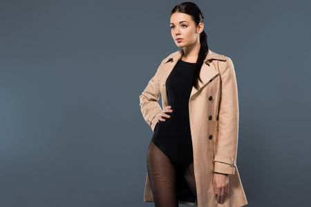 Woman in black pantyhose and beige trench isolated on dark background Stock Photo