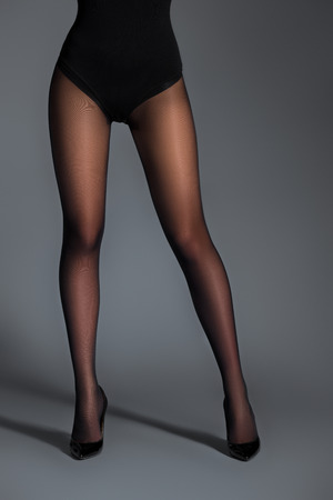 Slim woman in black pantyhose on dark background